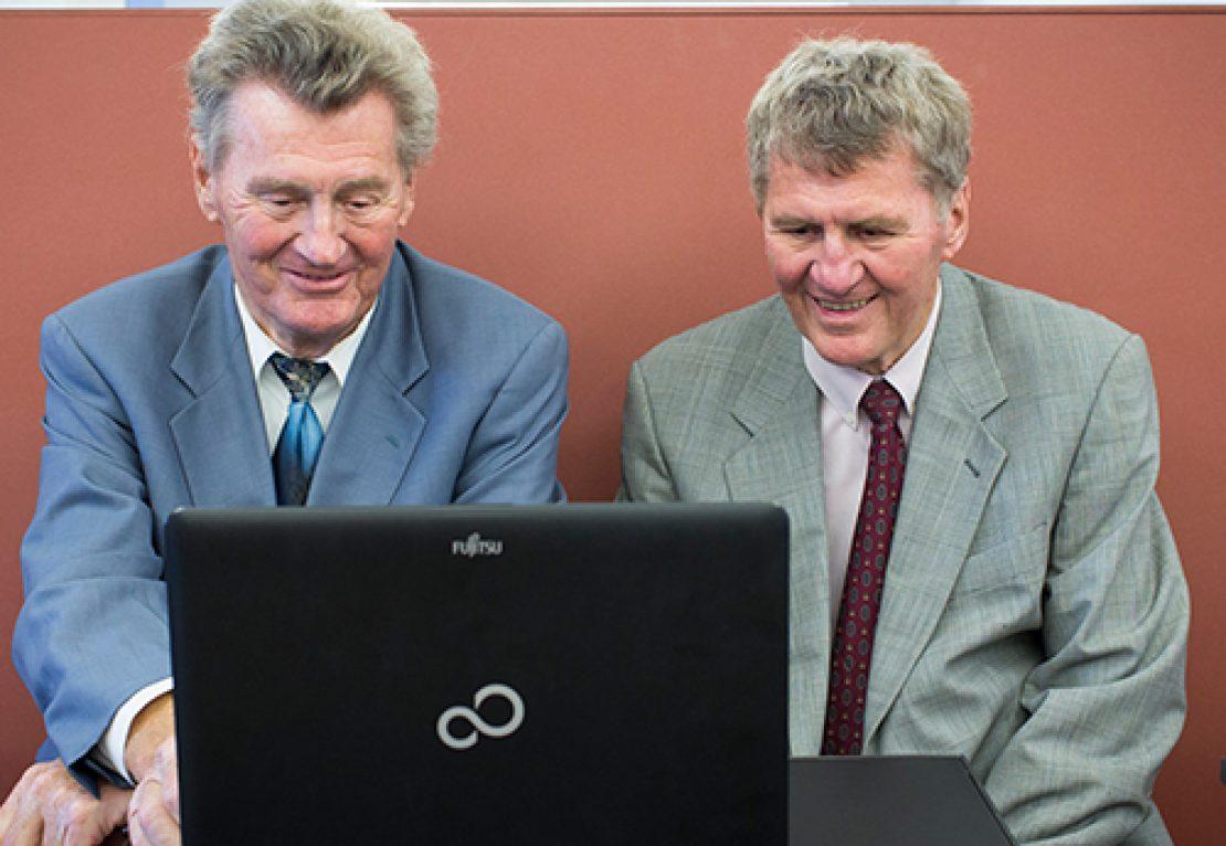 Zwei Alumni testen die TUM Online-Community auf einem Laptop.