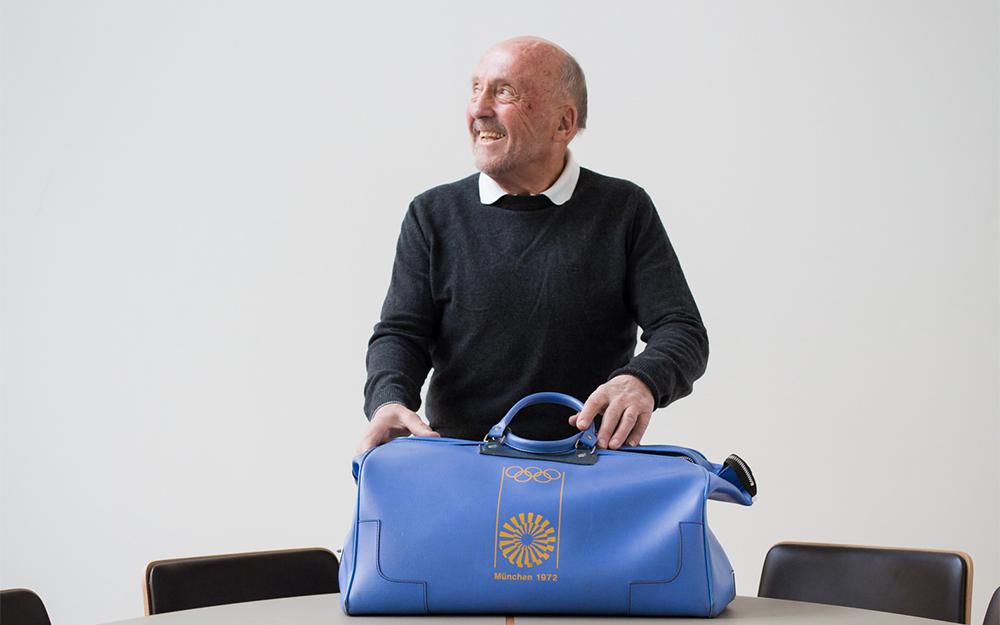 Klaus Wolfermann mit der lila Original-Olympiatasche in der Hand.