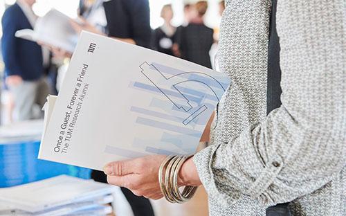 Eine Frau blättert in der Forscher-Alumni-Broschüre.