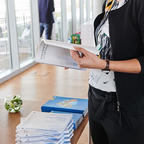 Eine Frau betrachtet Zeitschriften und Bücher, die auf einem Tisch ausliegen.