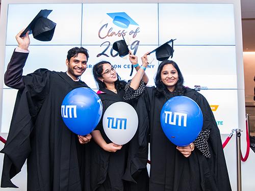 Alumni posen mit TUM Luftballons und Abschlussrobe.
