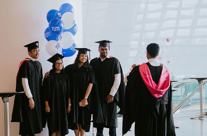 Vier TUM Absolventinnen und Absolventen machen ein Gruppenfoto mit TUM Luftballons.