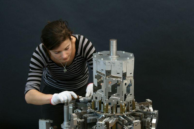 TUM Alumna Nora Eibisch – hier in der Werkstatt für wissenschaftliche Instrumente des Deutschen Museums in München – liebt es, aus den vielen Einzelteilen alter komplexer Maschinen ein funktionsfähiges System zu rekonstruieren