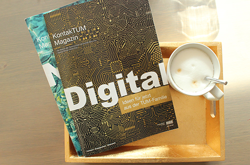 Two issues of the alumni magazine KontakTUM with coffee cup.