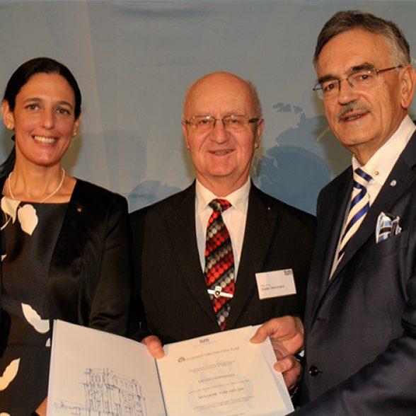 President Wolfgang A. Herrmann (r.) and Vice-President Dr. Ana Santos Kühn hand over the golden degree deed to gold degree holder Dieter Herrmann.