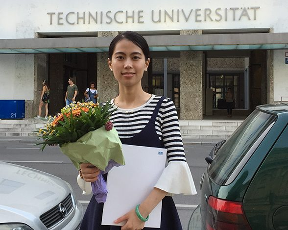 TUM Alumna Yijia Zhuang with her graduation certificate and a bouquet of flowers in from of the TUM main entrance.