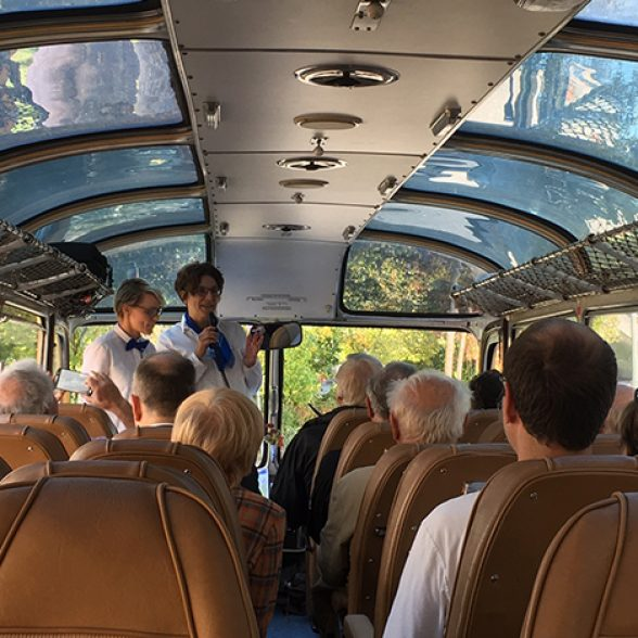 Two employees of TUM run the guided tour in the blue vintage bus
