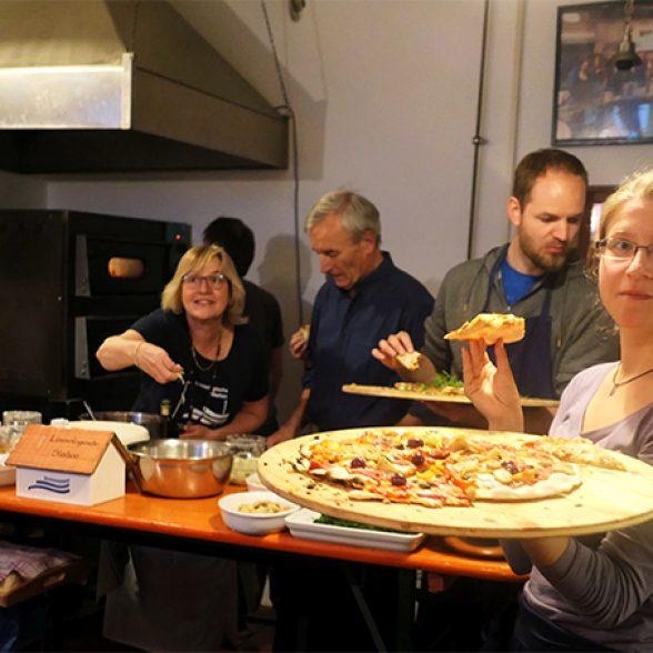 Alumni and employees baking pizza.