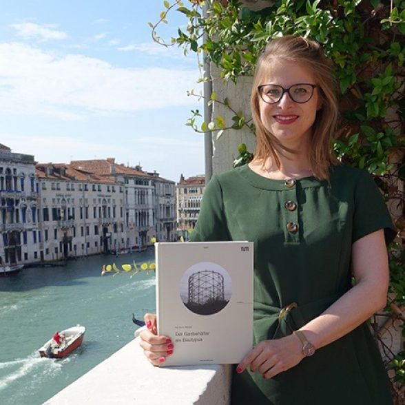 TUM Alumna Barbara Berger with her printed dissertation at the German Study Center in Venice.