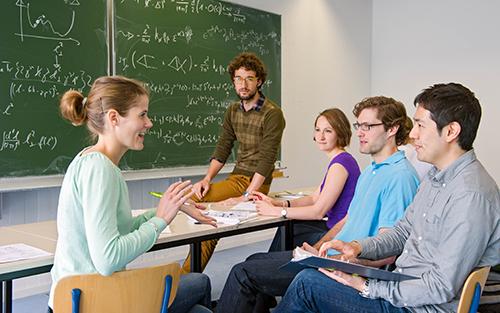 Studierendengruppe vor einer Tafel bei einer Besprechung.