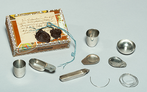 Cigar box with seals and hand-forged chemists' cutlery.