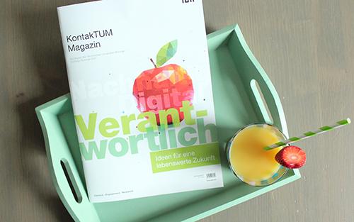 Ein Foto des Alumni-Magazins auf einem Tablett mit einem Orangensaft.